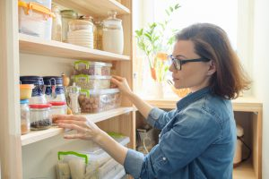 A woman looking at her pantry.