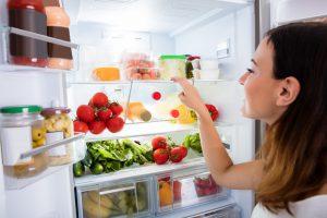 Woman looking at bins in fridge.
