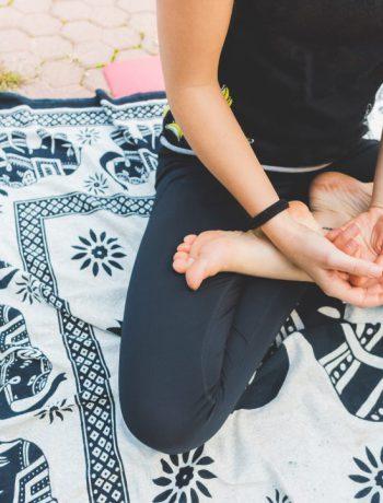 Person meditating on mat.