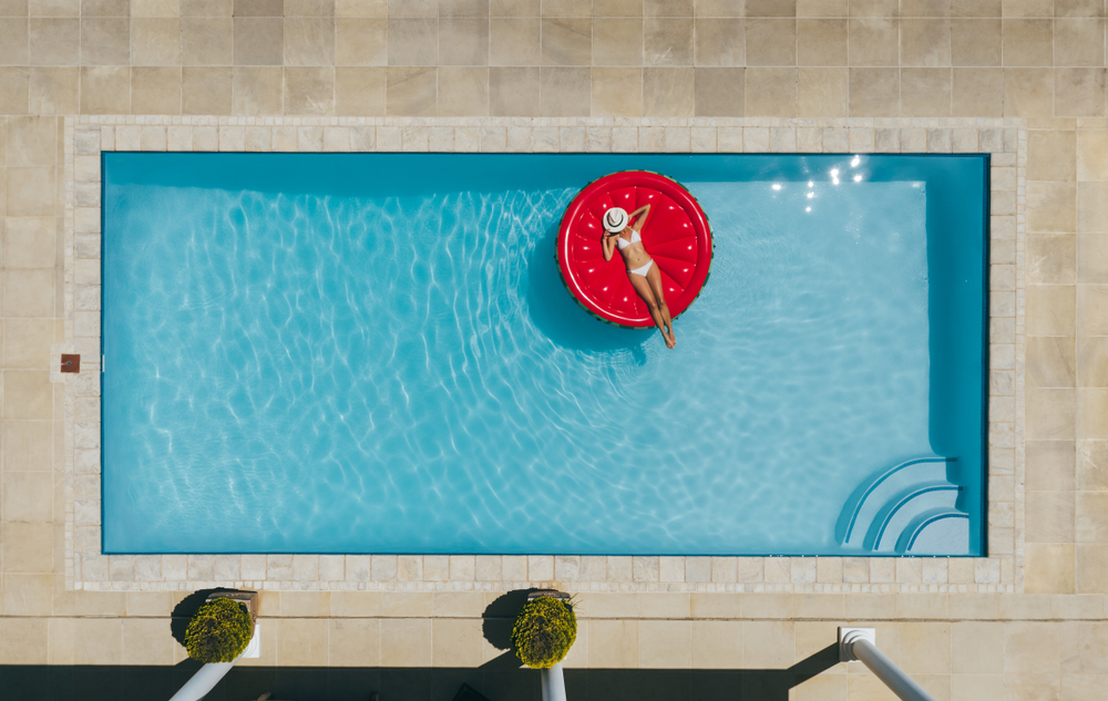 Woman laying on a raft in a pool.