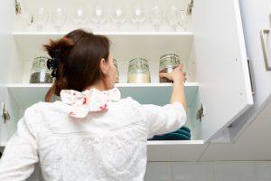 A woman organizing kitchen cabinets.