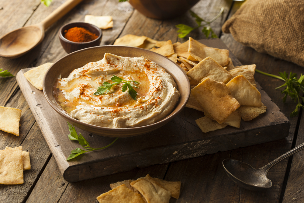 board with pita chips and a bowl of hummus
