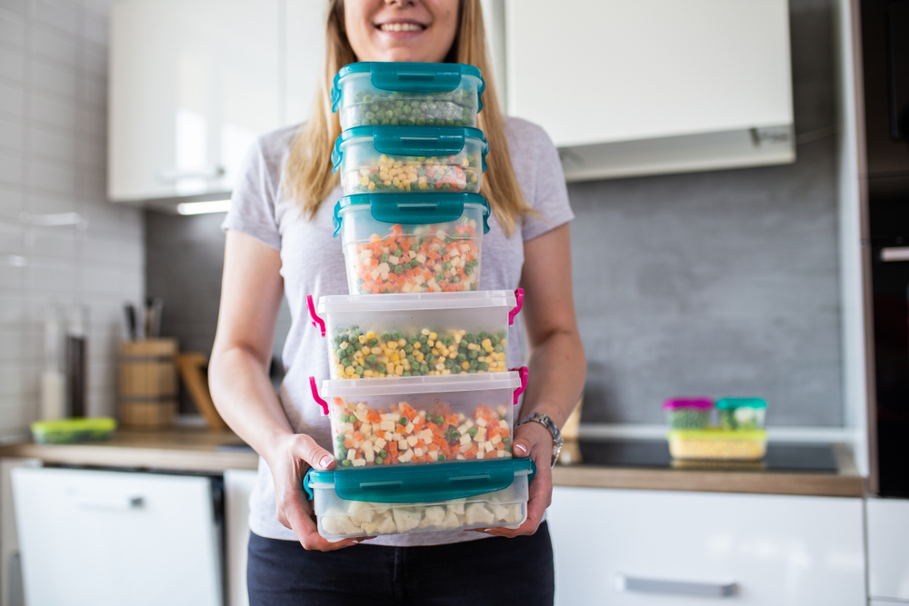 woman carrying plastic containers with food