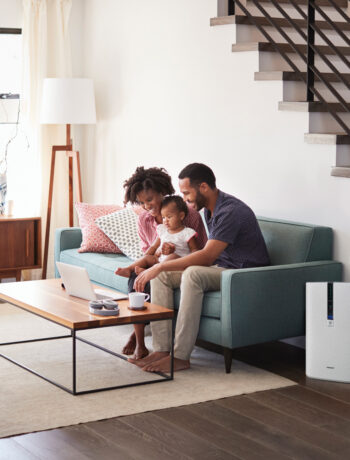couple sitting on couch next to an air purifier