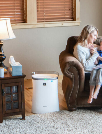Mother and son sitting by a Sharp air purifier