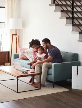 family sitting next to KC860U air purifier