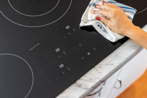 person wiping an induction cooktop