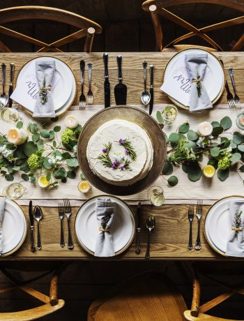 Table setting for five people with flowers.