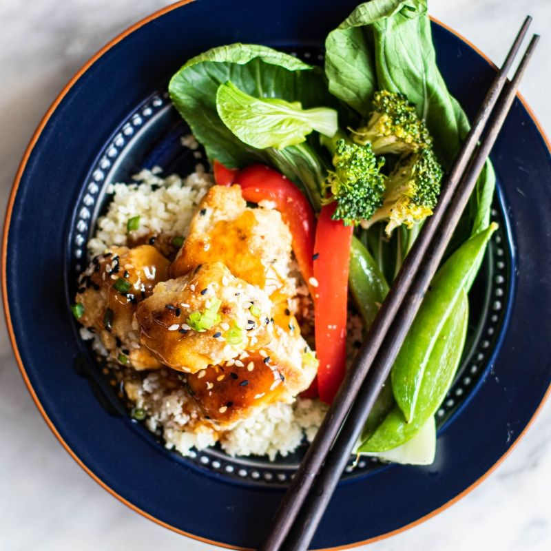 Sweet and sour chicken with broccoli and chopsticks.