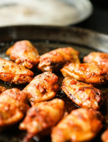 Wings in a pan on a stove.