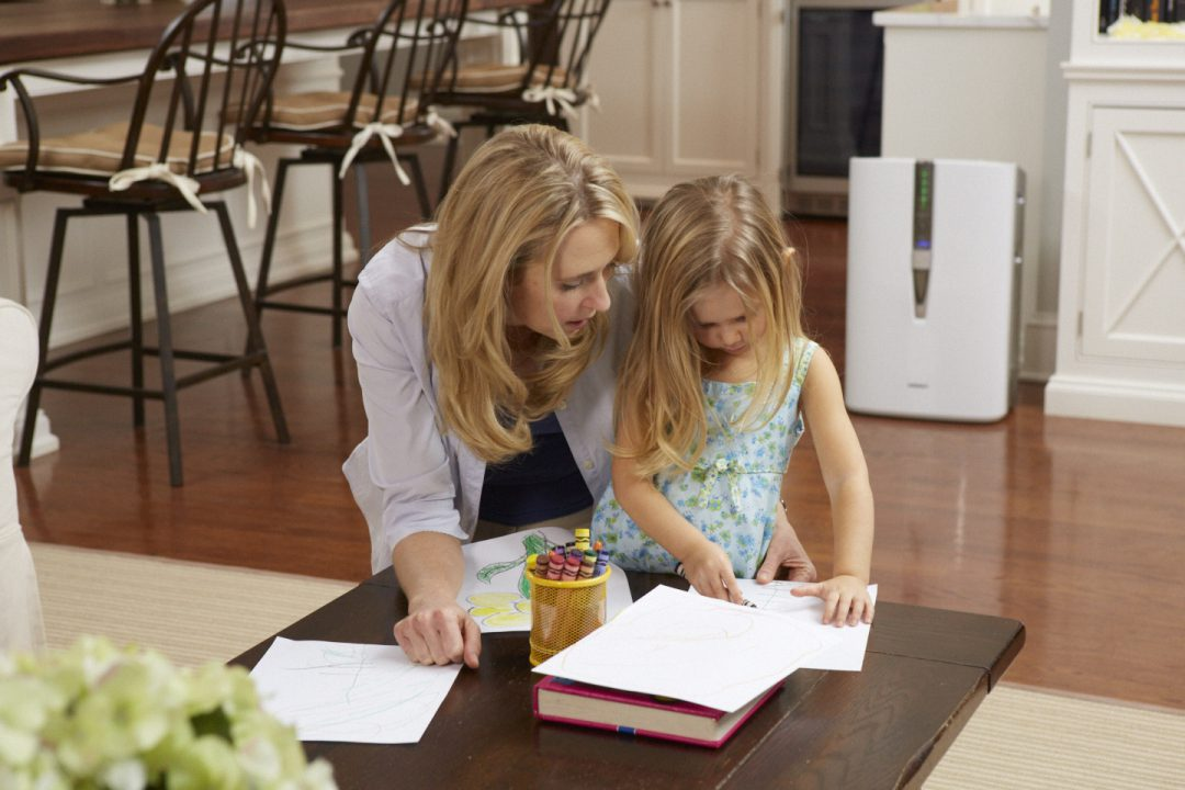 Mother and daughter coloring near a Sharp air purifier.