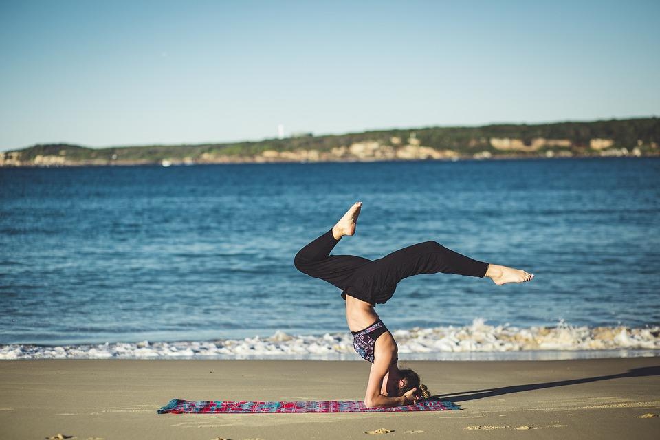 Woman practicing meditation alongside a body of water.
