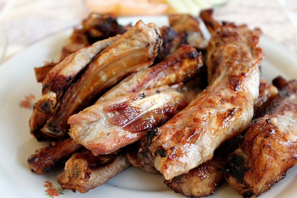 Oven baked ribs stacked upon one another on a white plate.
