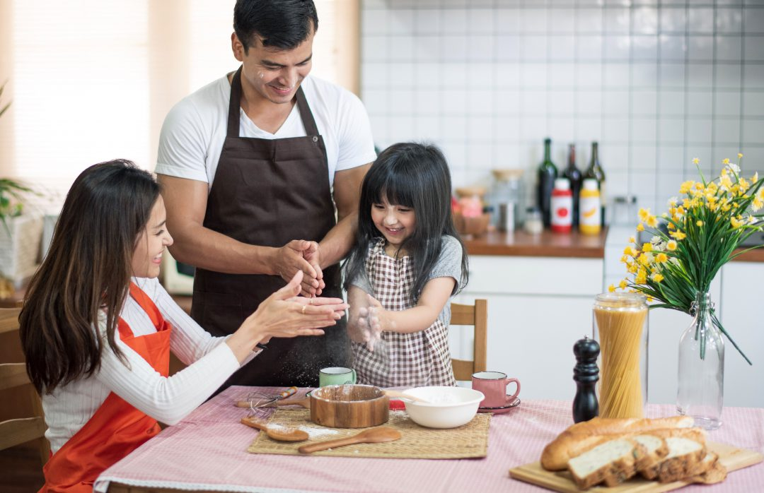 Family of three cooking in a kitchen preparing meals.