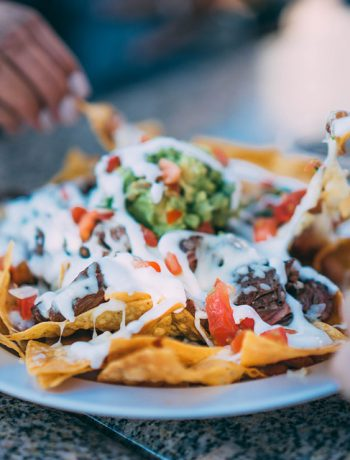 Nachos with toppings being spread apart and shared by three people.