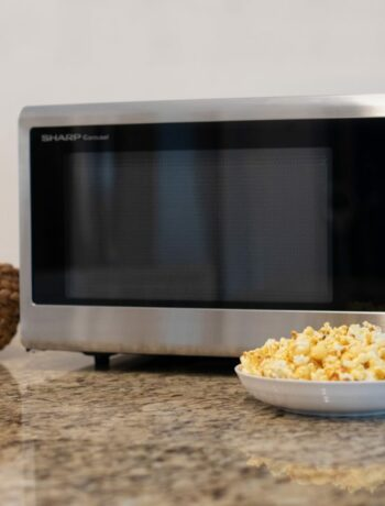 bowl of popcorn in front of a microwave