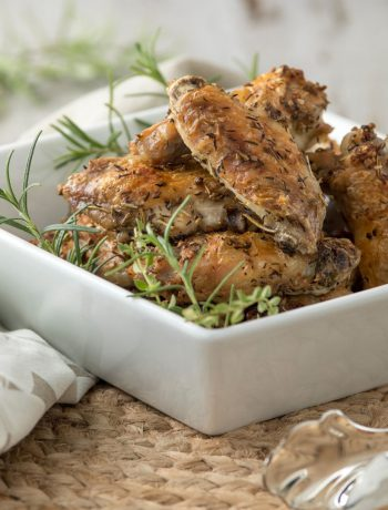 Chicken wings in a square dish on a wicker surface.