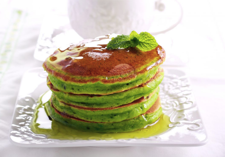 Matcha pancakes stacked upon one another on a white plate.