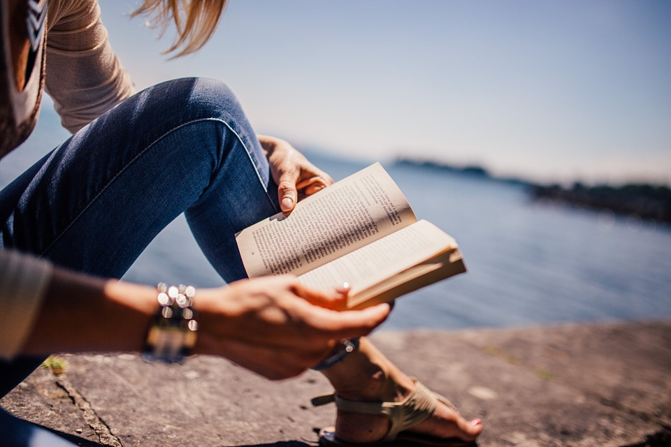 Woman reading a book on a rock next to a large body of water.