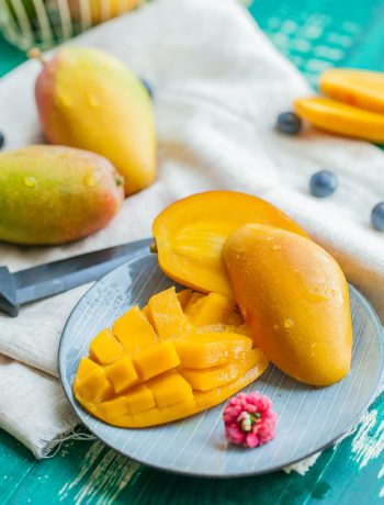 Mango dessert on a plate next to mangos.