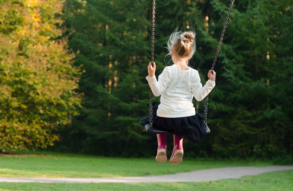 Young girl on a swing facing a wooded areas.