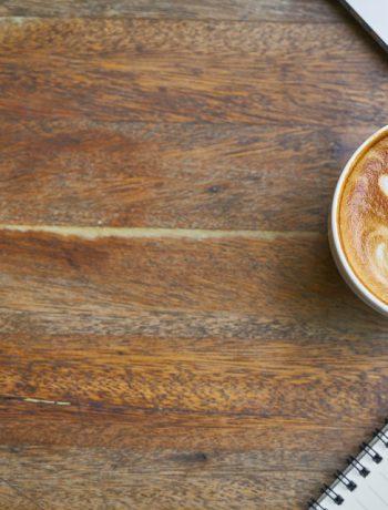 Coffee mug with a heart next to a workspace.