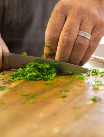 person chopping herbs on a cutting board