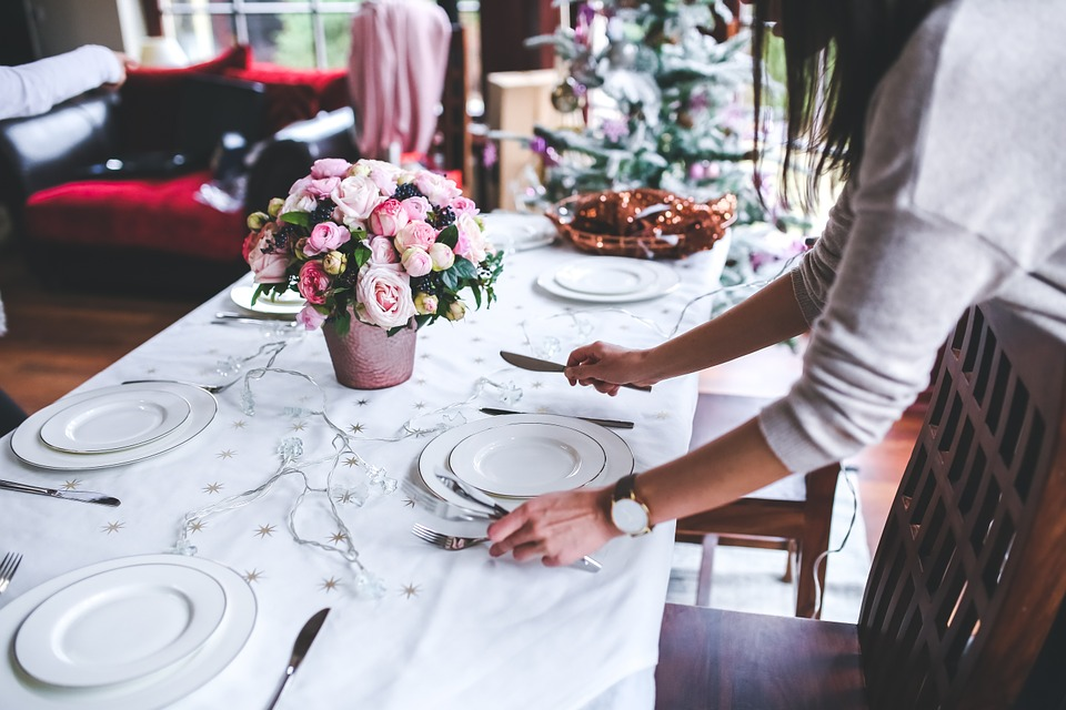 A woman setting a dinner table using a holiday setting.
