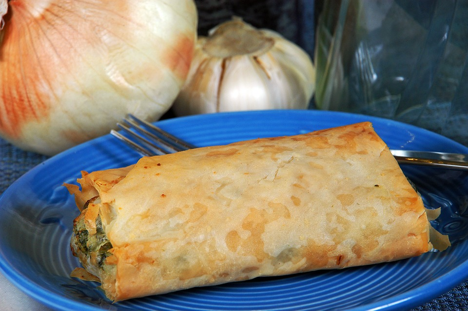 Spanakopita on a blue plate with onions in the background.