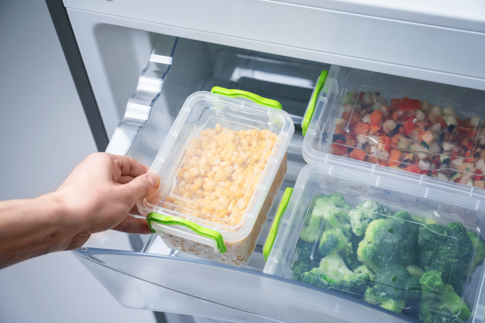 containers of food being put in a fridge drawer