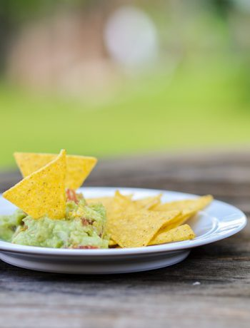 Guac and chips on a plate at an outdoor table.