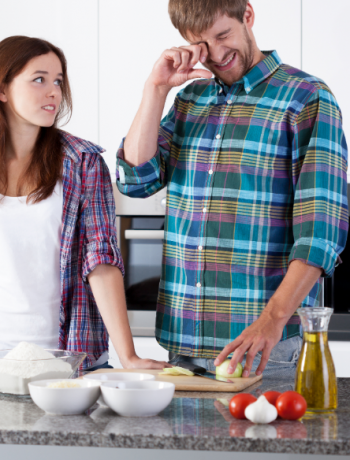 A young couple preparing food in a kitchen.