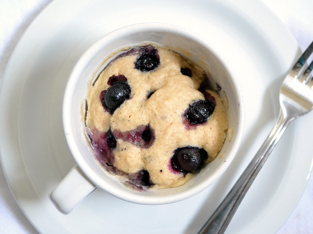 Blueberry mug cake on a plate next to a fork.