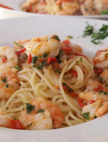 Shrimp scampi with spaghetti in a bowl.