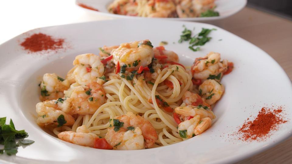 Shrimp scampi with spaghetti in a bowl.