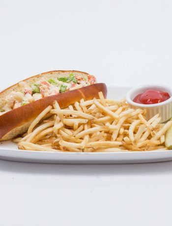 Lobster roll on a plate with french fries, ketchup, and a pickle.