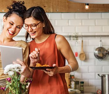 Two people looking at recipes on a tablet in a kitchen.