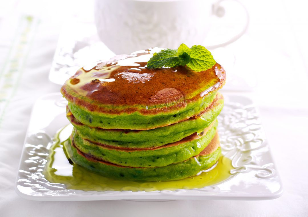 Matcha pancakes stacked upon each other on a white plate.