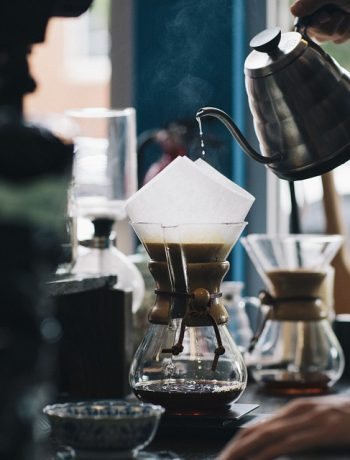 Coffee being poured into a jar using a funnel.