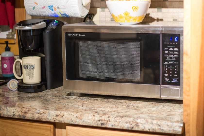 Sharp countertop oven next to coffee machine.