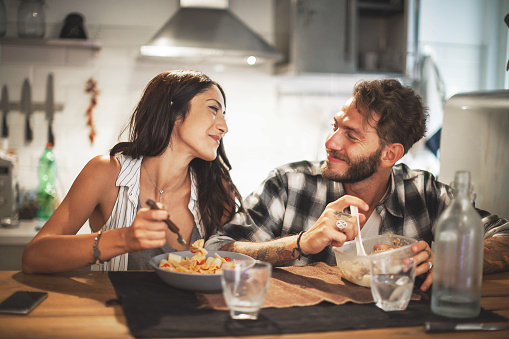 A young couple smiling at one another eating dinner in a kitchen.