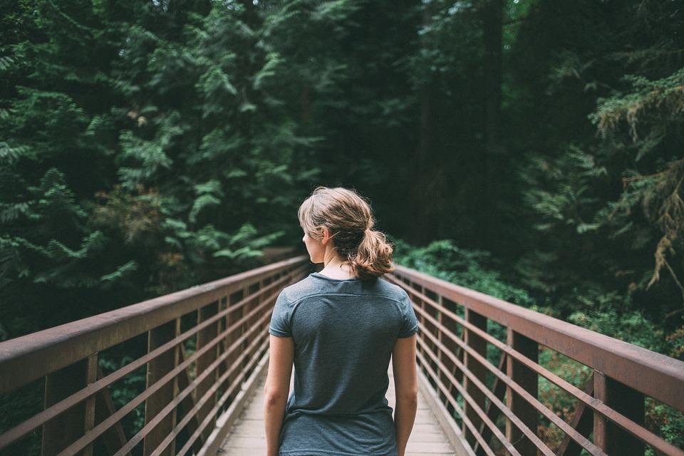 Woman outside on a pedestrian bridge enjoying nature.