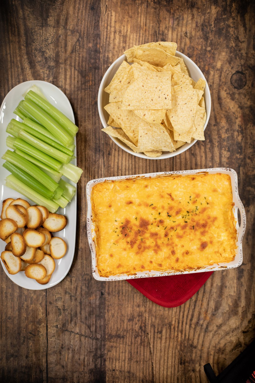 Buffalo dip on a table next to chips and celery.