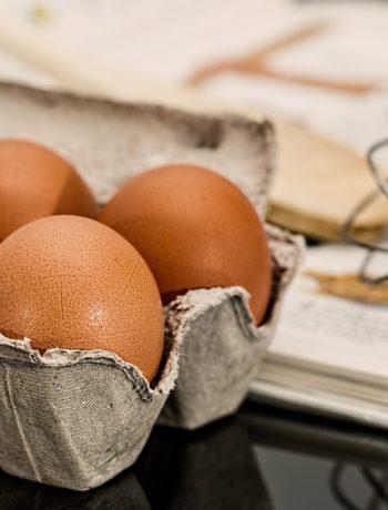 Eggs in a carton on a desk next to a cookbook.