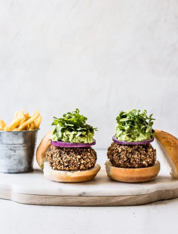 Two burgers on a wooden plate and jar of french fries.