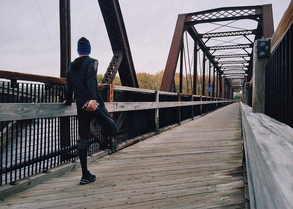 Jogger stretching prepared to cross a pedestrian bridge.