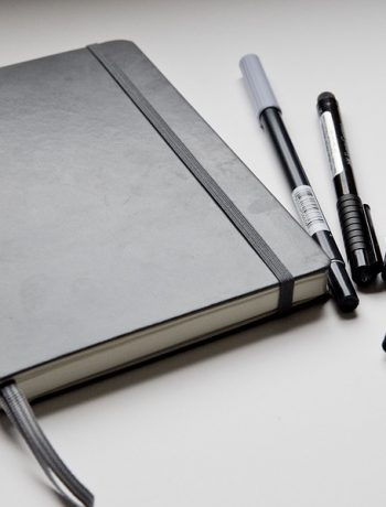 Grey journal next to different color pens.