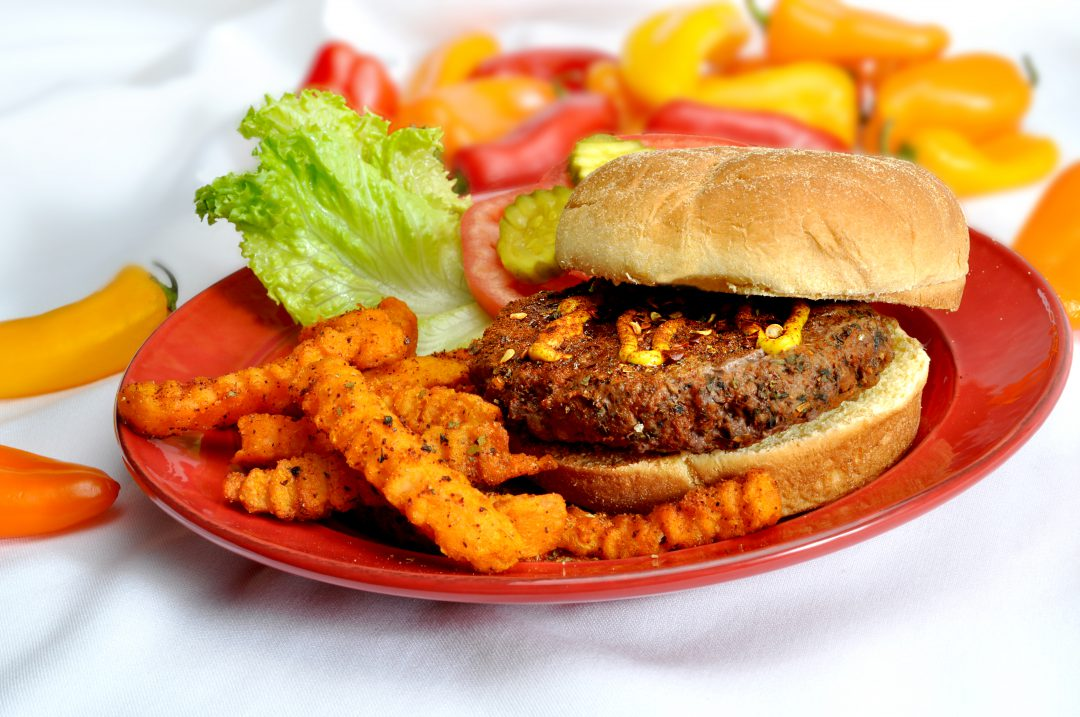 Cajun burger on a plate with sweet potato fries.