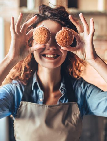 Woman holding two muffins in front of her eyes while smiling in a kitchen.