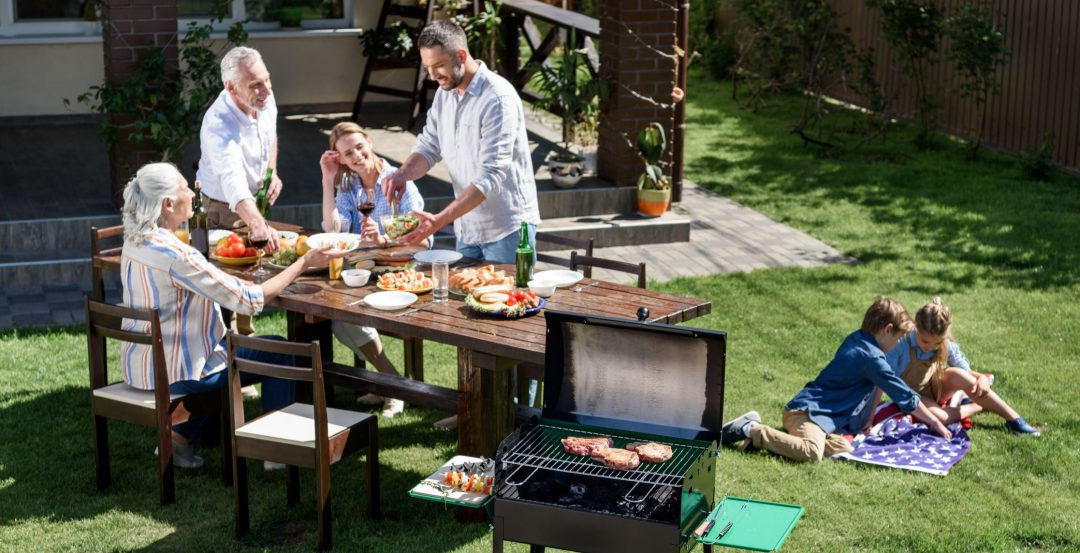 Family barbeque with a table, grill, and children playing on the grass.